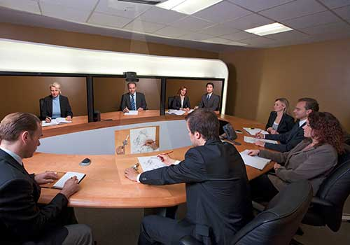 A group of people sitting at a half circle desk video conferencing with four other people