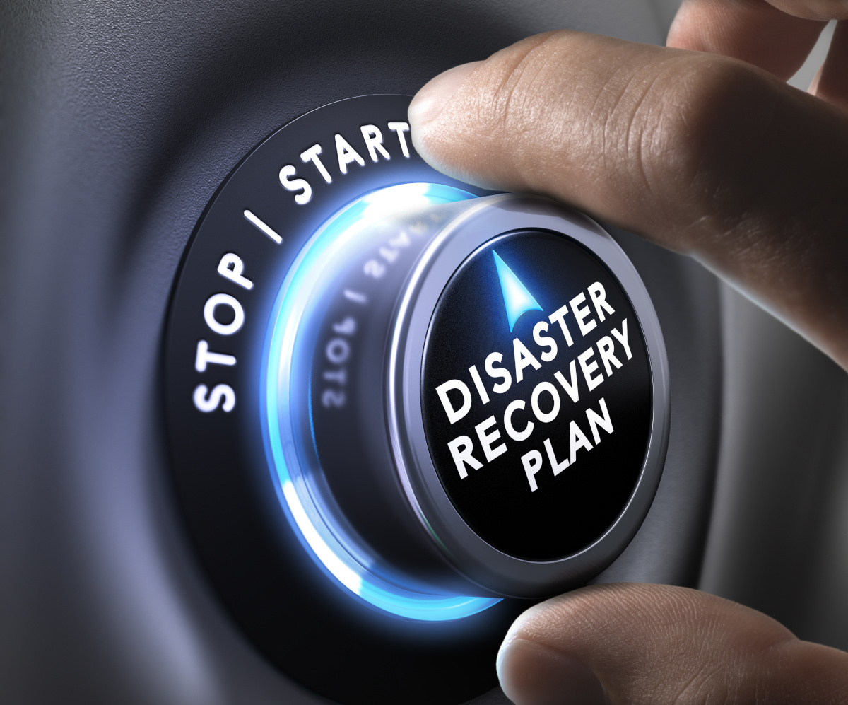 Close up of a hand turning a dial that says 'Disaster Recovery Plan' to Start, as the dial glows bright blue