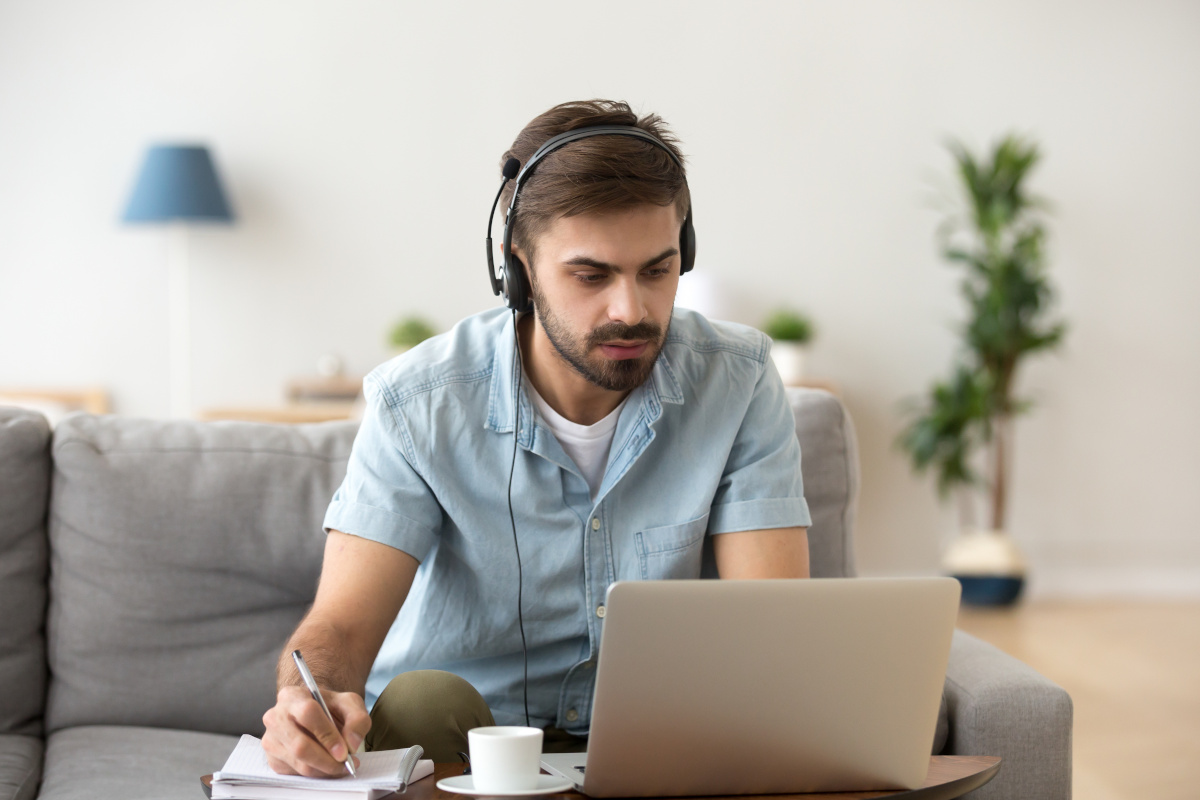 A man using a headset while working form home on his laptop