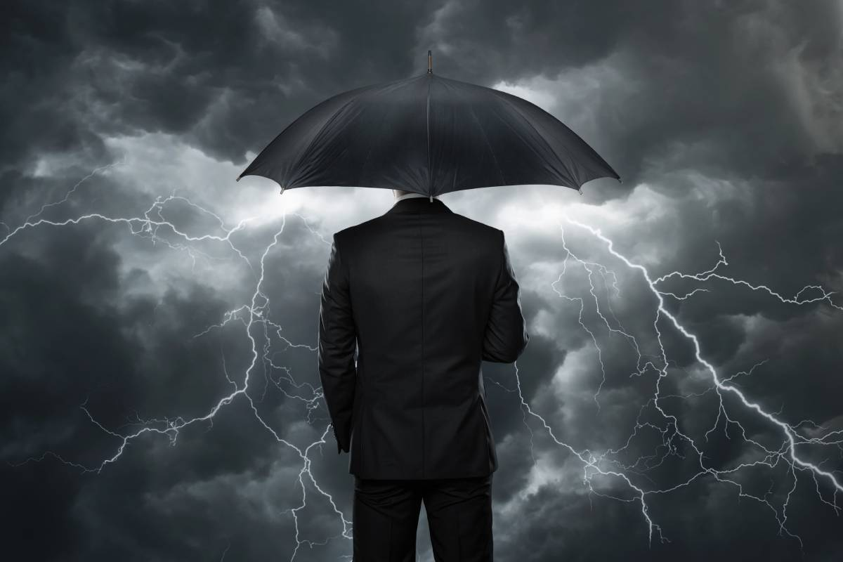 A man in a suit holding an umbrella while facing a storm